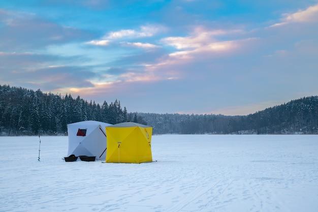 Tenda da pesca sul ghiaccio su un lago ghiacciato al tramonto
