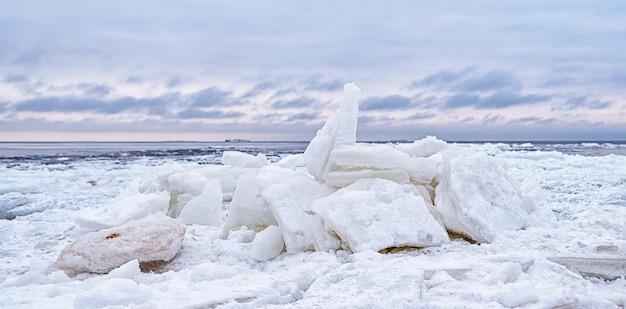 Lastrone di ghiaccio che si rompe contro la riva con ghiaccio marino durante il freddo inverno. ripiano del ghiaccio.