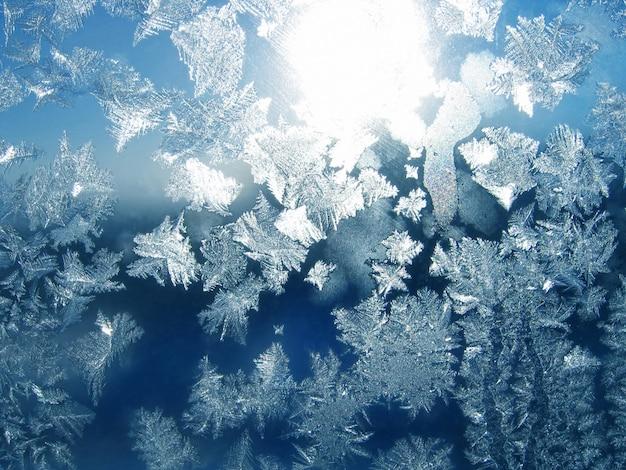 Modello di ghiaccio e luce solare sul vetro invernale