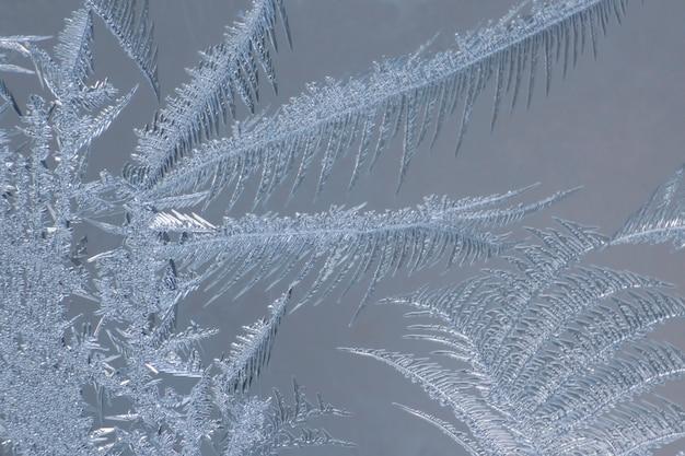 Modelli di ghiaccio e acqua ghiacciata su vetro. trame e sfondi naturali. modelli di ghiaccio su frozen