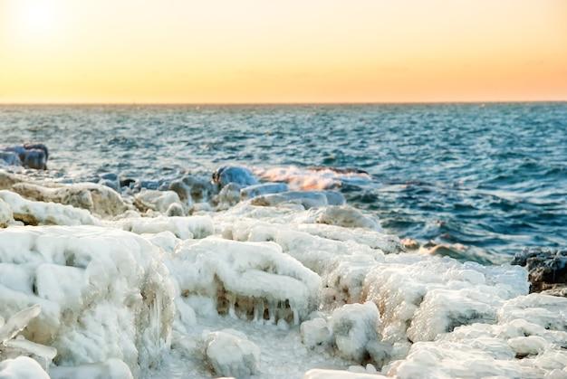 Ghiaccio sulle rocce vicino al mare con un bellissimo tramonto arancione