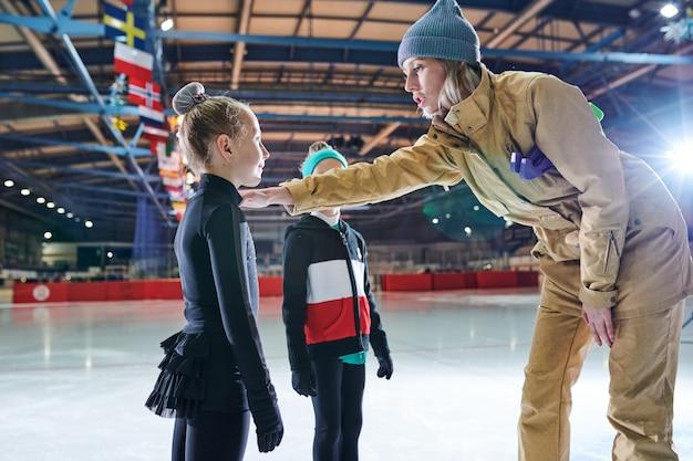Allenatore di pattinaggio sul ghiaccio motivating kids