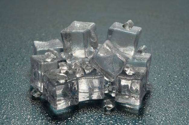 Pietra di ghiaccio sulla superficie riflettente dello sfondo con gocce, idea di un ambiente freddo o di un luogo molto freddo
