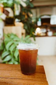 Caffè americano ghiacciato in bicchiere da asporto su tavolo in legno