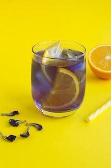 Tè di fiori blu ghiacciato con arancia in un bicchiere su sfondo giallo. posizione verticale. avvicinamento.