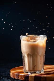 Caffè ghiacciato in un bicchiere su sfondo scuro