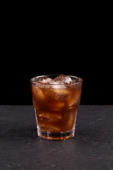 Caffè ghiacciato in un bicchiere. piano di lavoro in pietra scura. sfondo nero. copia spazio.