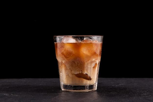 Caffè ghiacciato in un bicchiere alto con crema versata sopra. sfondo scuro, copia dello spazio.