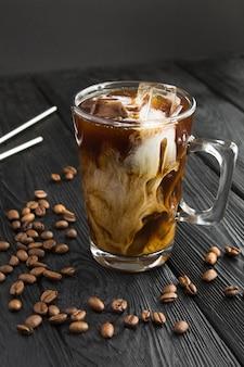 Caffè ghiacciato con latte nella tazza di vetro su sfondo nero. posizione verticale.