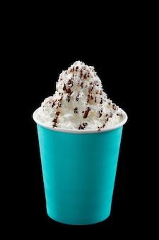 Caffè freddo con panna montata, gelato e topping in un bicchiere di plastica blu su sfondo nero black