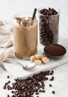 Caffè freddo ghiacciato al caramello con latte e fagioli crudi e cucchiaio con caffè macinato e zucchero di canna su tavola di marmo su luce.