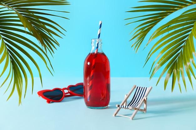 Cocktail di mirtillo rosso ghiacciato in bottiglia con foglie di palma e accessori estivi su sfondo blu