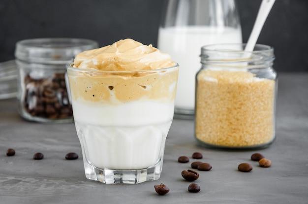 Iced dalgona coffee un caffè montato cremoso e soffice alla moda con latte in un bicchiere su uno sfondo scuro