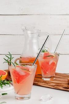 Bevanda ghiacciata al pompelmo con rosmarino. copia spazio, verticale