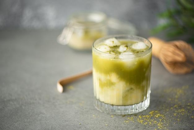 Matcha verde ghiacciato con succo di limone in un bicchiere su un tavolo grigio
