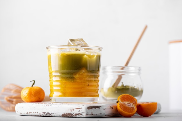 Matcha verde ghiacciato con succo d'arancia in un bicchiere, primo piano
