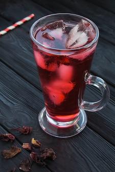 Ibisco ghiacciato o tè karkade nel bicchiere sullo sfondo di legno nero. posizione verticale. avvicinamento.