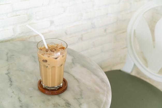 Bicchiere di caffè latte ghiacciato sul tavolo nella caffetteria bar