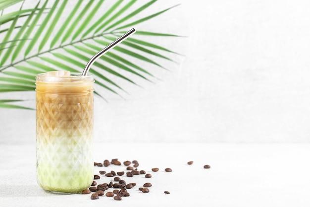 Caffè matcha ghiacciato con latte di cocco e ghiaccio su sfondo bianco