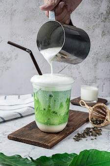 Tè verde al latte freddo o tè al latte tailandese in vetro sul tavolo