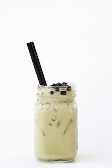 Tè verde latte ghiacciato con bublle boba su sfondo bianco