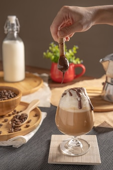 Caffè moka ghiacciato servito con topping di panna montata e sciroppo di cioccolato in un bicchiere di vino posto sulla tavola di legno