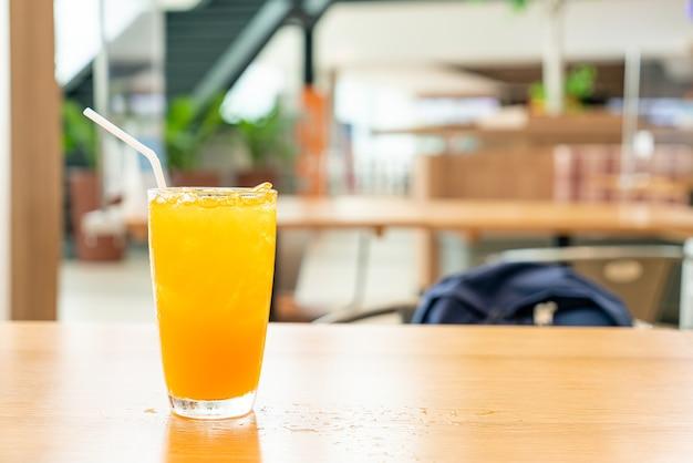 Succo d'arancia ghiacciato sul tavolo di legno nel ristorante caffetteria