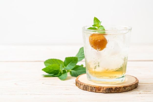 Succo di prugna ghiacciato con soda e menta piperita sul tavolo di legno - bevanda rinfrescante
