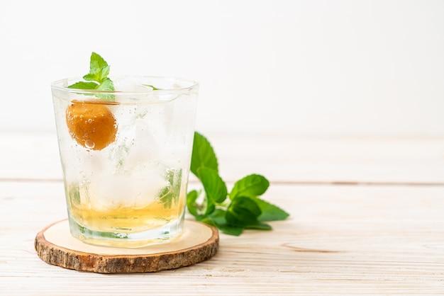 Succo di prugna ghiacciato con soda e menta piperita sul tavolo di legno