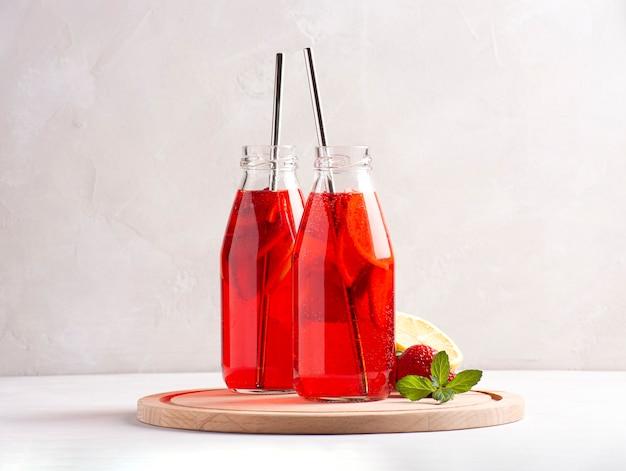 Limonata ghiacciata alla fragola in bottiglie con tubi di metallo si trova su un tavolo di cemento grigio.