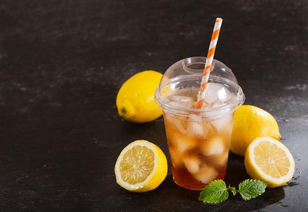 Tè freddo in vetro di plastica con frutta fresca sul tavolo scuro