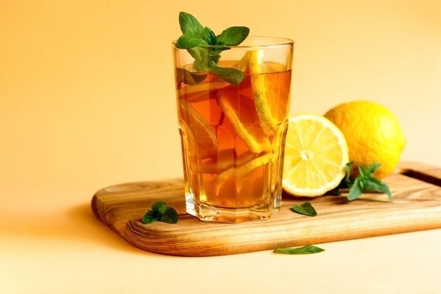 Tè freddo al limone e menta su fondo giallo