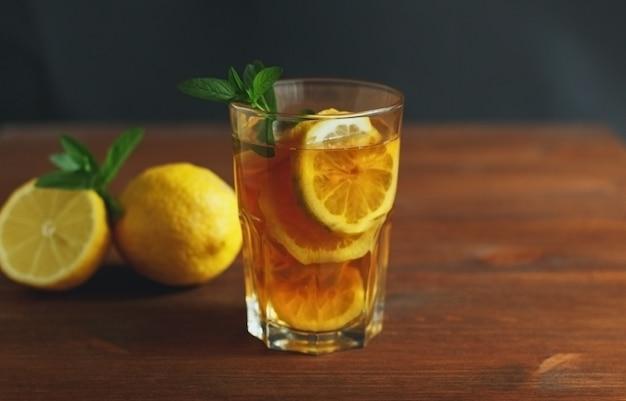 Tè freddo con fettine di limone e menta su fondo in legno