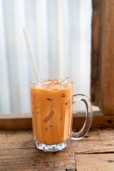 Bicchiere di tè al latte tailandese ghiacciato nel ristorante bar