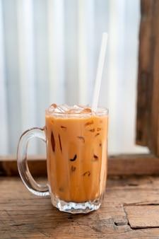 Bicchiere di tè al latte tailandese ghiacciato nel ristorante caffetteria