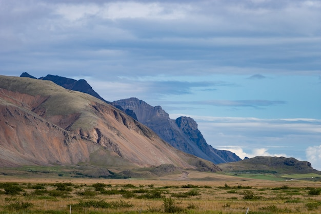 Paesaggio islandese con montagne, cielo blu ed erba verde in primo piano. parte del fiordo occidentale.