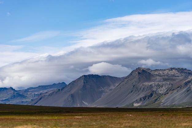 Paesaggio islandese con montagne, cielo blu ed erba verde in primo piano