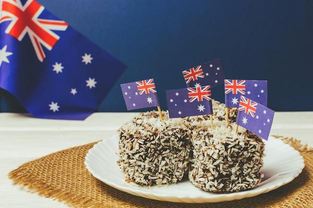 Iconico cibo tradizionale australiano per le feste, torte lamington su uno sfondo rosso, bianco e blu. bandiera dell'australia.