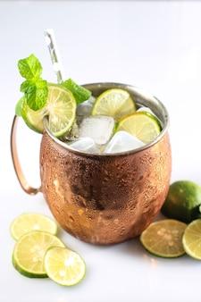 Icy cold moscow mules con ginger beer, lime e vodka, guarnire con una foglia di menta. isolato su sfondo bianco