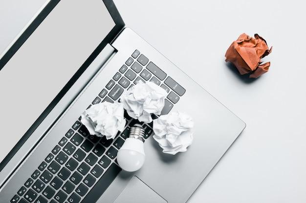 Concetto di business idea. computer portatile, palline di carta stropicciata, lampadina a led sul tavolo grigio. vista dall'alto, piatto