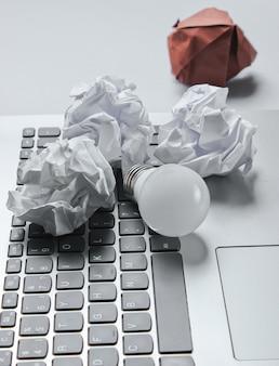 Concetto di business idea. computer portatile, palline di carta stropicciata, lampadina a led sul tavolo grigio