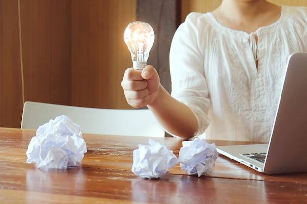 Idea della persona di affari che tiene creatività di concetto della lampadina con le lampadine.