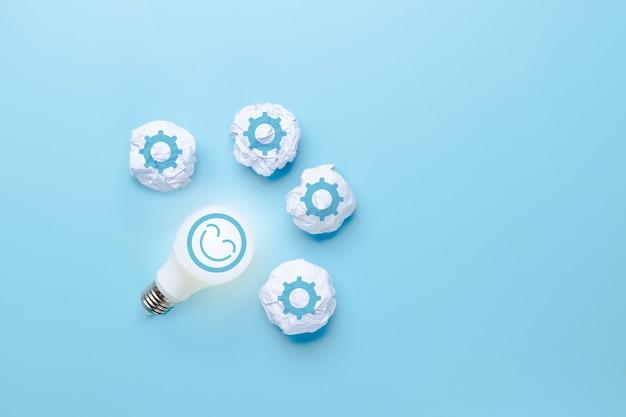 Idea e innovazione creativa con l'icona del sorriso sul viso e la lampadina e l'icona della carta straccia dell'icona del lavoro su sfondo blu