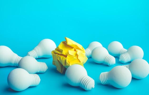 Concetti di idea e creatività con palla di carta stropicciata e lampadina