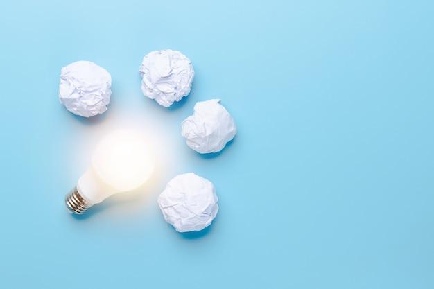 Idea e innovazione con il salvataggio del concetto mondiale, illuminazione della lampadina con carta straccia su sfondo blu