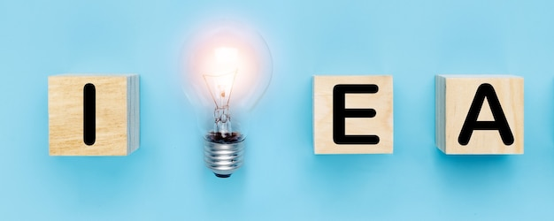Idea e nuovo concetto di pensiero creativo, lampadina con parola idea su blocco di legno su sfondo blu