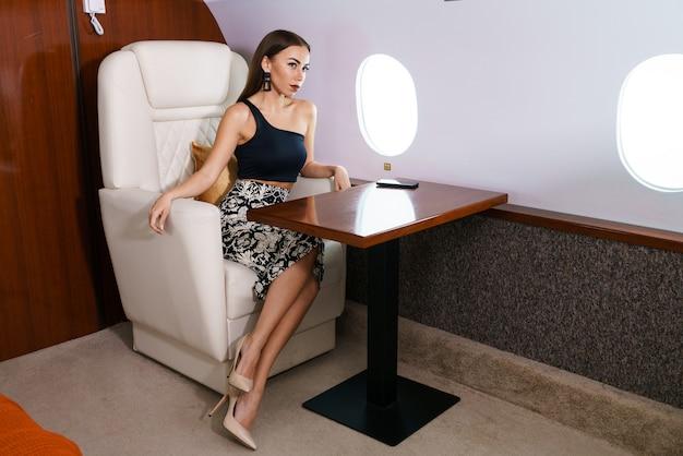Donna ideale una donna moderna in abiti eleganti sorride mentre è seduta vicino alla finestra in un primo momento