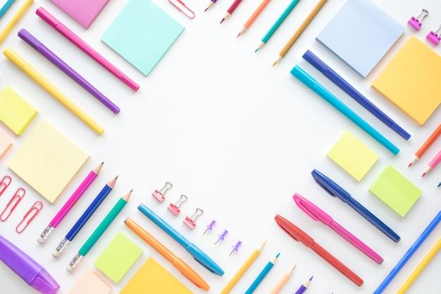 Idee concetti di creatività con la disposizione piatta di cancelleria colorata su spazio bianco