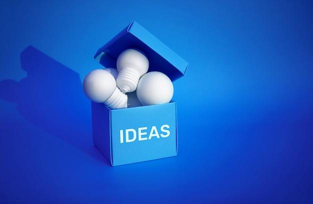 Idee concetti di ispirazione con un gruppo di lampadine nella casella blu sullo spazio di sfondo di colore. creatività aziendale. motivazione per il successo.