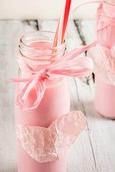 Idee per san valentino, due bottiglie di frappè rosa Foto Premium